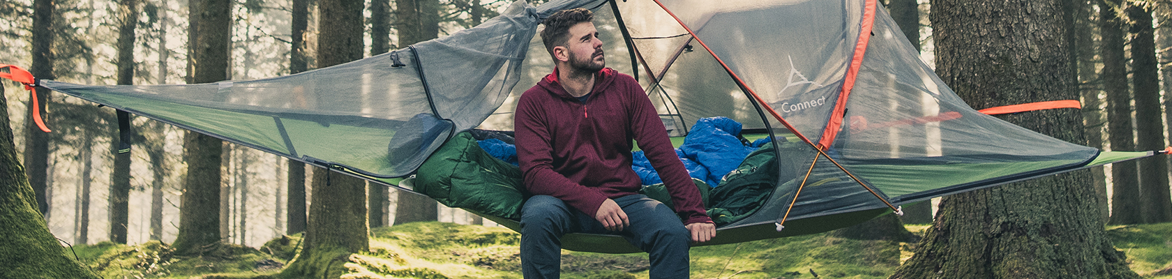 Two people sat drinking from a mug outside of a tent.