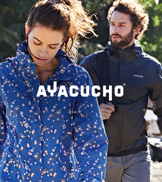 Man and woman walking away from old cars wearing Ayacucho gear.