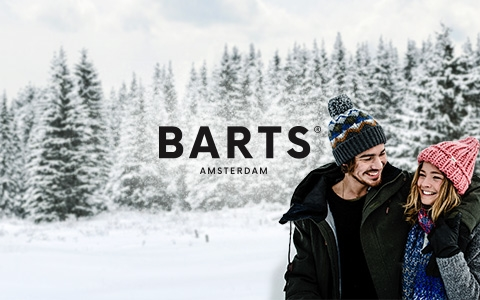 Couple wearing Barts clothes in snow covered forest