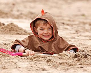 Child plays in the sand on the beach in Littlelife clothing