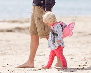 Parent and child walk on beach in LottleLife gear