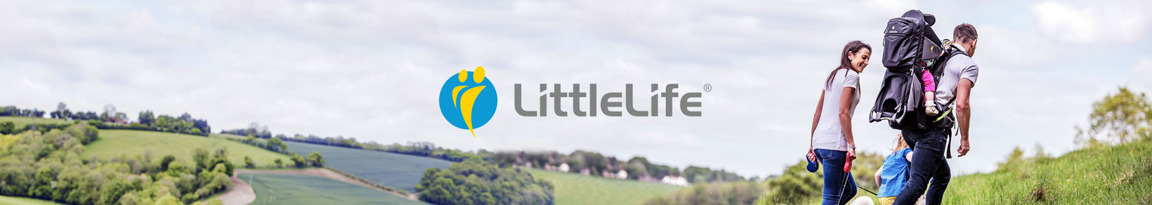A man is carrying one child  in a LittleLife carrier on his back while another child is holding his hand and a woman is holding dog's lead, walking through fields on a cloudy day, with the littlelife logo in the center.