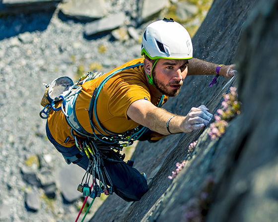 Man climbing rocks wearing Mountain Equipment gear