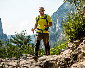 A solo man walks up a rocky mountain in Montane gear and walking poles