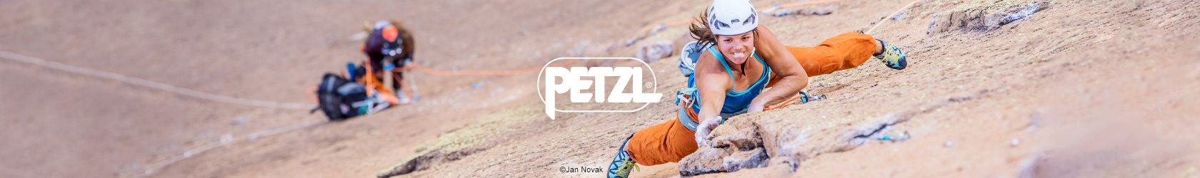 Two people are almost at the top of a rock, wearing and using Petzl gear.