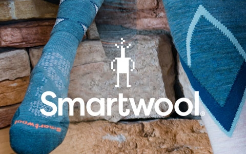 Person's feet by a stone wall, wearing Smartwool socks