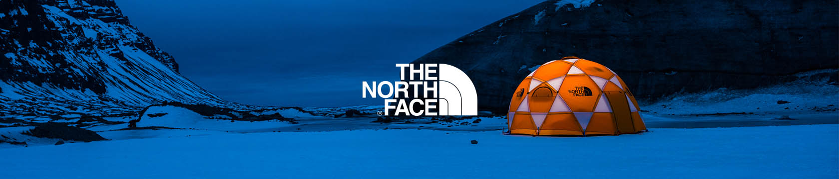 The North Face orange and white tent among snow and mountains in the dark