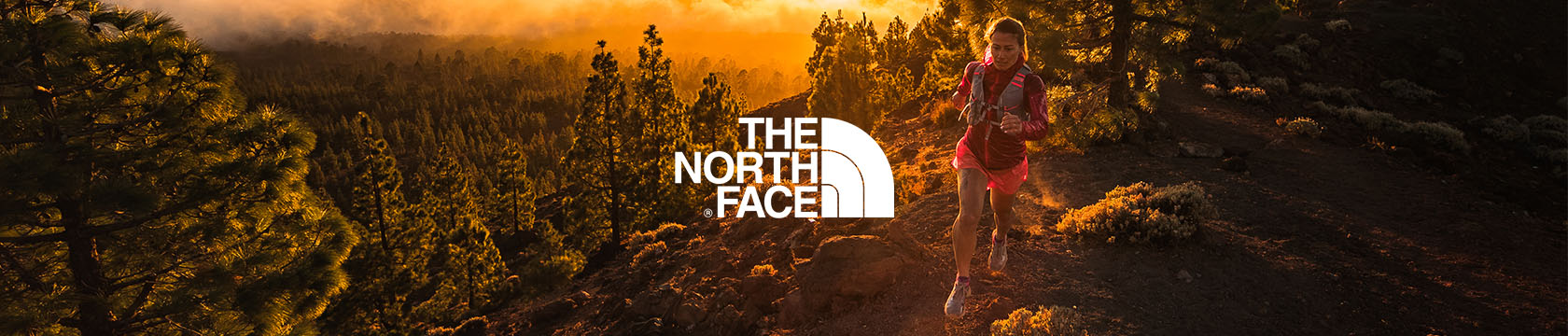 Woman jogging on hillside wearing The North Face gear