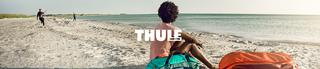 People on a beach with a Thule duffel.