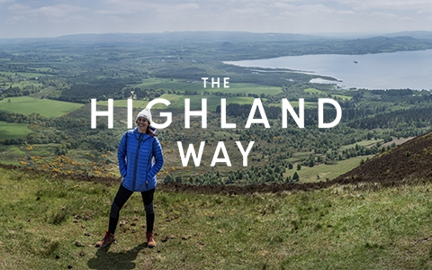 The Highland way - a woman is standing on a hill, wearing Columbia gear.
