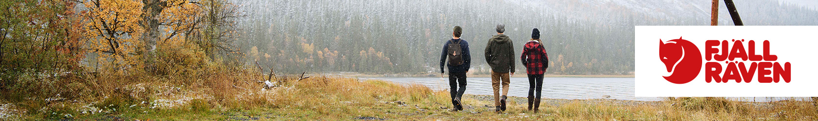 Three people are walking away from the camera and towards the lake, surrounded by mountains and trees, wearing Fjallraven gear.