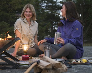 Two women laugh while drinking and sitting in front of a fire
