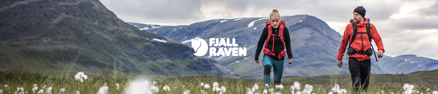 A couple walking in mountains, wearing Fjallraven gear.