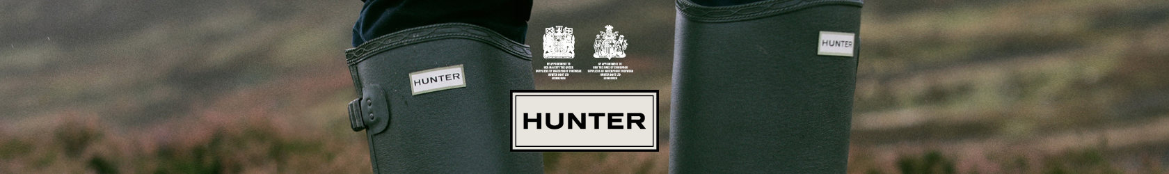 Green Hunter wellies in the outdoors with the Hunter logo in the middle.