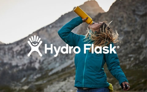 A woman is drinking out of a yellow Hydro Flask bottle somewhere outdoors, surrounded by mountains.