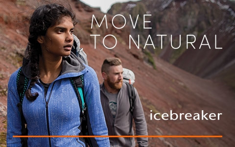 Man and women walking through rocky terrain wearing Icebreaker clothing