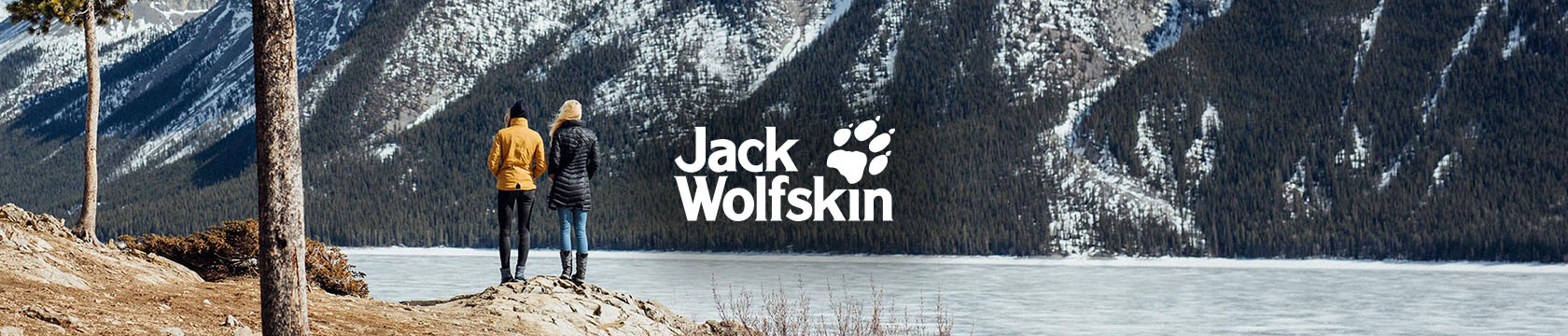 Two people in Jack Wolfskin gear standing by the lake among mountains that are covered by trees and snow.
