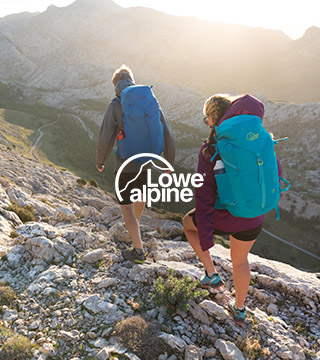 Woman and man hiking carrying Lowe Alpine backpacks.