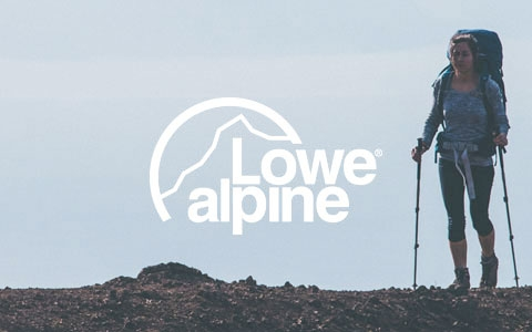 A woman stood at the top of a hill, wearing a Lowe Alpine backpack and holding walking sticks