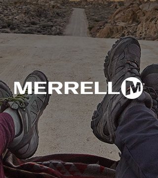 Female and male legs in Merrell footwear in the middle of a sandy road