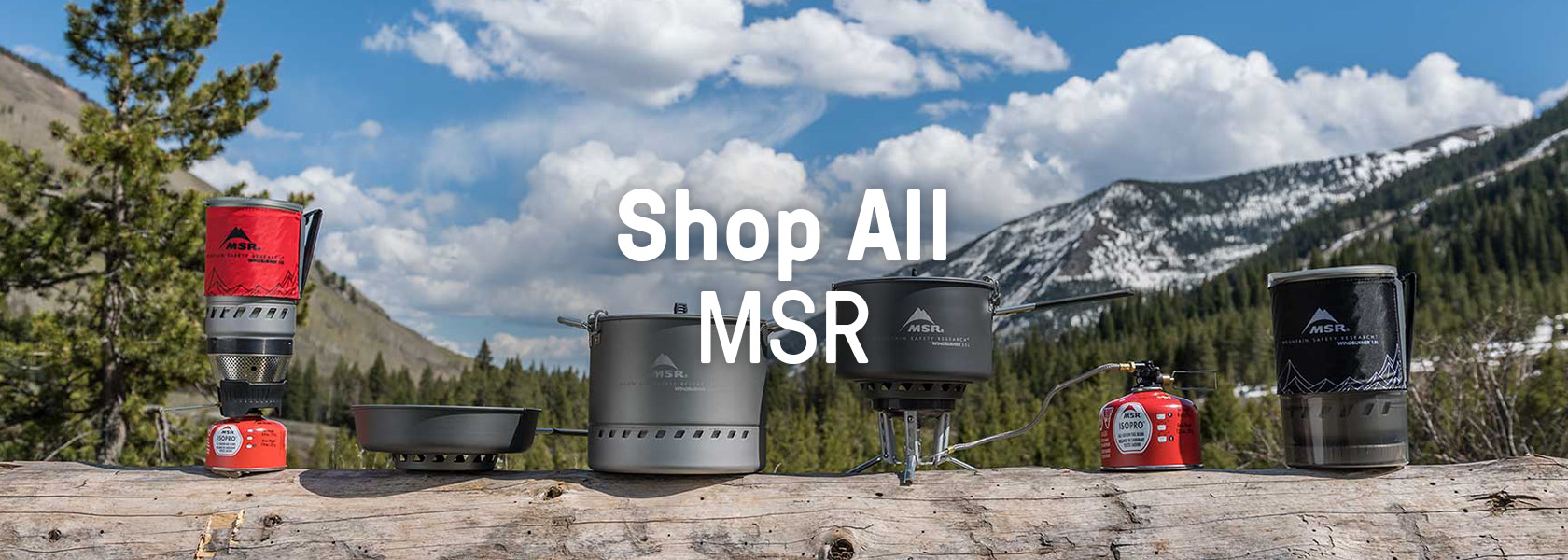A range of MSR outdoor kitchen equipment standing on a log.