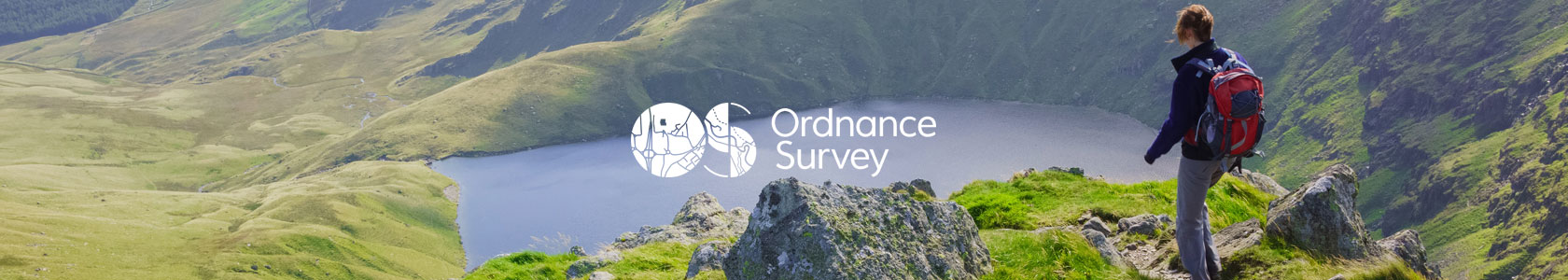 A woman is walking on a hill not far from a lake, using Ordnance Survey map