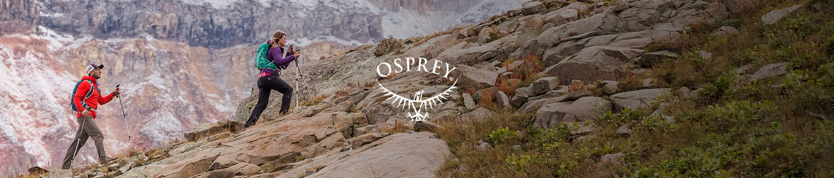A couple with Osprey backpacks walking up a rocky hill somewhere in the mountains.