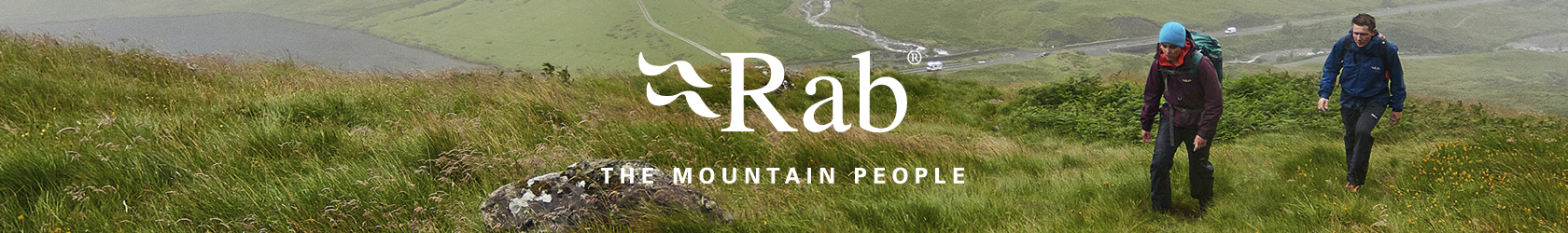 2 People wearing and using Rab gear are walking up a grassy hill.
