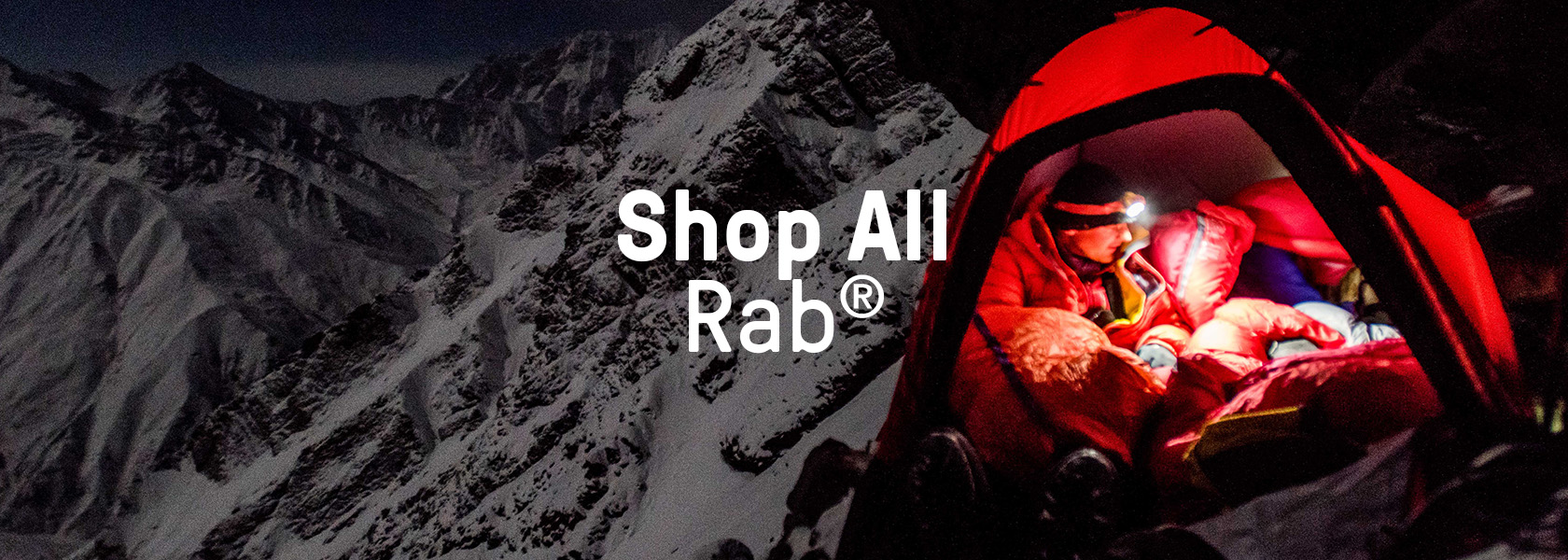 Man in tent keeping warm with Rab gear.
