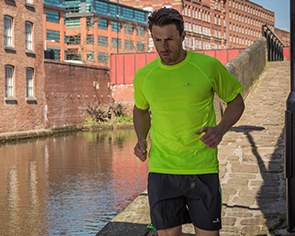 Man running next to river in Ronhill clothing.