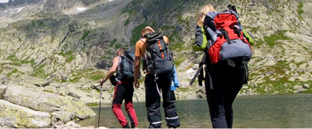 A group of camping people walking along water and mountains