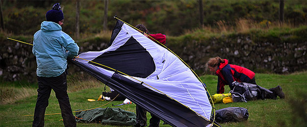 People outdoors trying to put a tent up