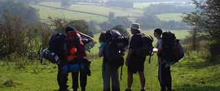 A group of people with camping gear stopped outdoors to check their navigation