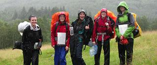 A group of camping people fully equipted under the rain