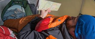 Man in sleeping bag and tent reading map