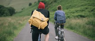 Two people on bikes with Millican Backpacks