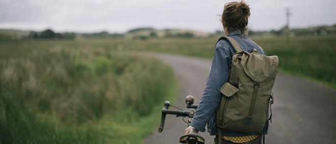 Woman next to bike while wearing her Millican Maverick Backpack