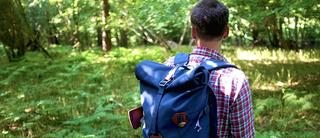 Man walks through the woods with his Millican rucksack