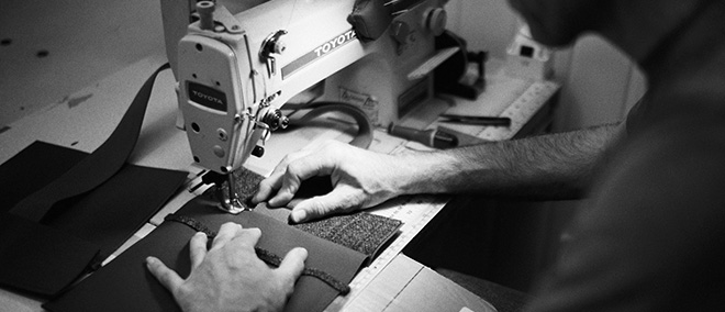 Man stitches together a sustainable millican bag