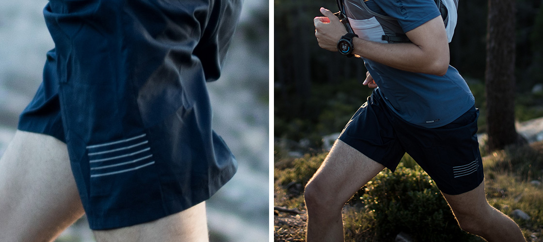 Man running through forest in work out wear, emphasis on his blue shorts