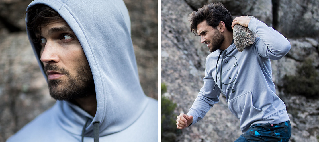 Man in Grey hoodie, carrying a rock on his shoulder running up more rocks