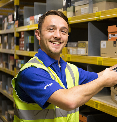 Man scanning a box at a warehouse and smiling at the camera