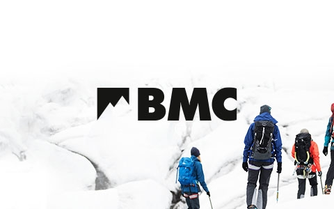 BMC logo in black on a white snowy background with 4 people to the right of the screen wearing ski gear
